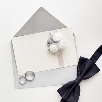 Bovenaanzicht vlinderdas en ringen bruiloft concept