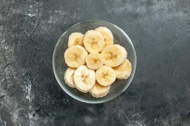 Bovenaanzicht voedingsbron verse bananen gehakt in een glazen pot mes op grijze achtergrond