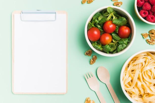 Bovenaanzicht voedsel containers met frambozen, salade en pasta met lege klembord