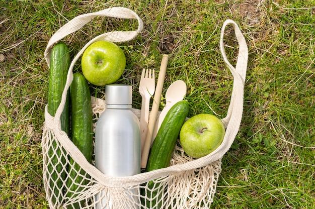 Bovenaanzicht voedsel in herbruikbare zak op gras