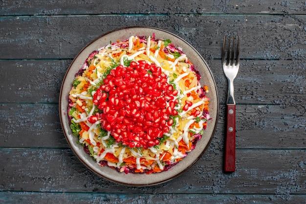 Bovenaanzicht voedselschaal met zaden van granaatappel en mayonaise naast de vork op de grijze tafel
