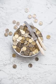 Bovenaanzicht volledige plaat van euromunten op marmeren tafel.