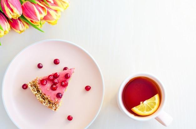 Bovenaanzicht voor ontbijt, ochtend met bloemen tulpen, cake, thee in roze mok op witte achtergrond.