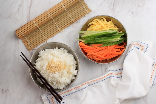 Bovenaanzicht voorbereiding ingrediënt gimbap (koreaanse roll rice) maken. witte rijst (bap) met nori zeewier of laver met diverse ingrediënten, zoals wortel, kyuri (komkommer), worst, kimchi
