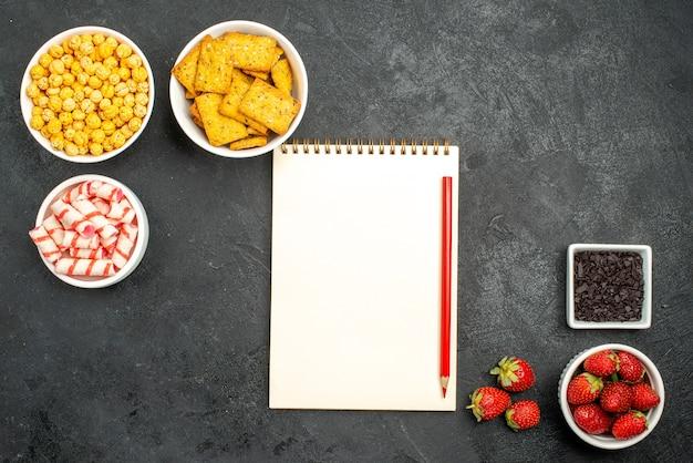 Bovenaanzicht voorbereiding snack recept met chocolade kruimels aardbeien mooie snoepjes op een zwarte achtergrond met vrije ruimte
