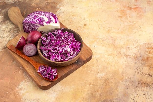 Bovenaanzicht voorbereiding van verse groentesalade met rode kool en uien op een snijplank op een houten tafel met kopieerruimte