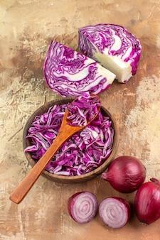 Bovenaanzicht voorbereiding voor een gezonde salade met een rode kool en uien op een houten ondergrond met kopieerruimte