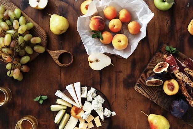 Bovenaanzicht voorgerechten tafel wijn snacks fruit jamon kaas
