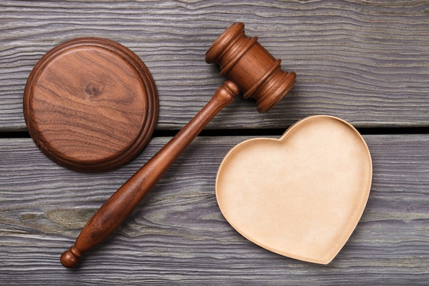 Bovenaanzicht voorzittershamer met houten hartvorm. concept huwelijk en huwelijkscontract. grijze houten achtergrond.