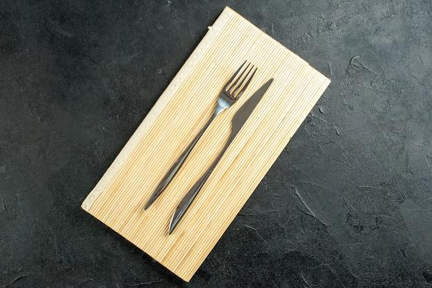 Bovenaanzicht vork en mes op beige houten bord op zwarte tafel met vrije ruimte