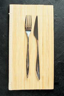 Bovenaanzicht vork en mes op beige houten bord op zwarte tafel