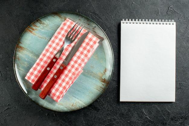 Bovenaanzicht vork en mes op rood wit geruit servet op ronde plaat notebook op donkere tafel