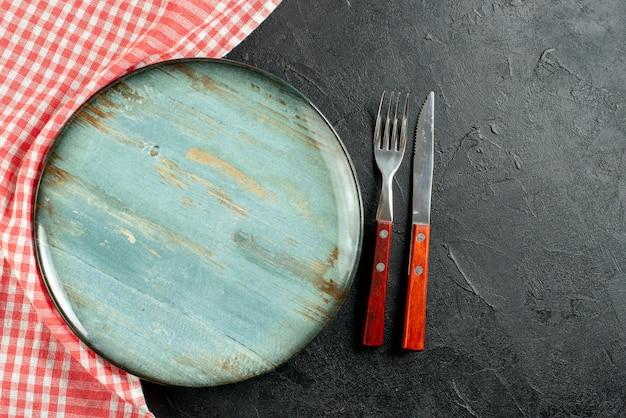 Bovenaanzicht vork en mes rood wit geruit servet ronde plaat op donkere tafel met kopie ruimte