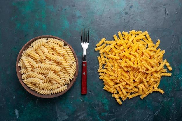 Bovenaanzicht vormde italiaanse pasta anders gevormde kleine pasta op het donkerblauwe bureau