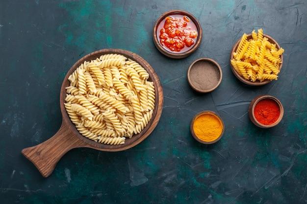 Bovenaanzicht vormde italiaanse pasta heerlijk uitziende kleine pasta op het donkerblauwe bureau