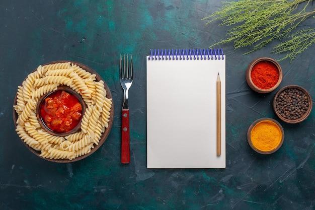 Bovenaanzicht vormde italiaanse pasta met blocnote en verschillende kruiden op de donkerblauwe achtergrond