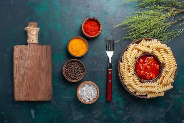 Bovenaanzicht vormde italiaanse pasta met kruiden op de donkerblauwe achtergrond