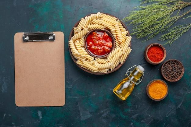 Bovenaanzicht vormde italiaanse pasta met olie en verschillende kruiden op donkerblauwe achtergrond