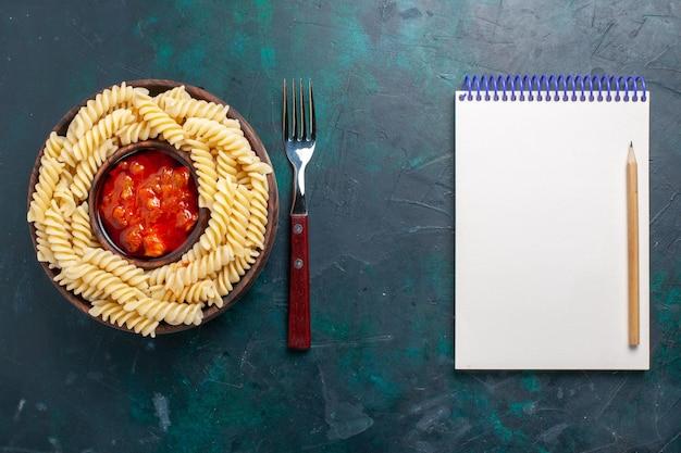 Bovenaanzicht vormde italiaanse pasta met tomatensaus en blocnote op donkerblauwe achtergrond
