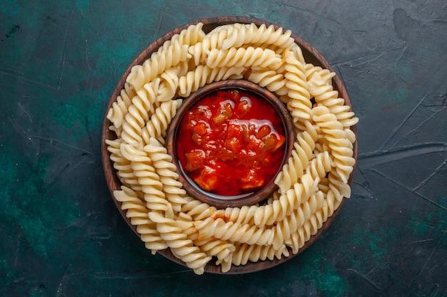 Bovenaanzicht vormde italiaanse pasta met tomatensaus op donkerblauwe achtergrond