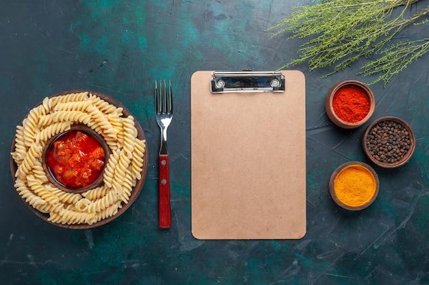 Bovenaanzicht vormde italiaanse pasta met verschillende kruiden op het donkerblauwe bureau