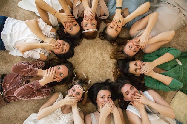 Bovenaanzicht vriendinnen mond verbergen door handen lachen ontspannen liggende cirkel samen op henparty