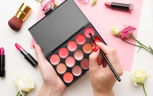 Bovenaanzicht vrouw cosmetische producten uitproberen