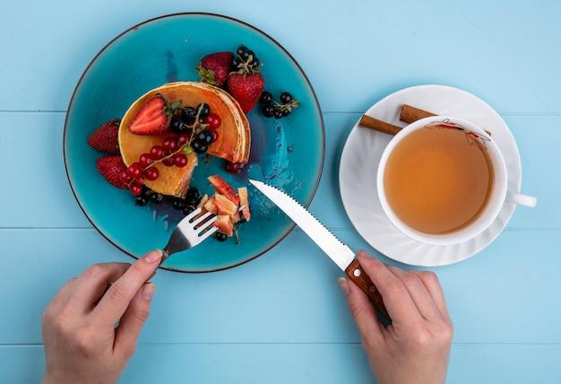 Bovenaanzicht vrouw eet pannenkoeken met aardbeien, rode en zwarte bessen en een kopje thee op een blauwe tafel