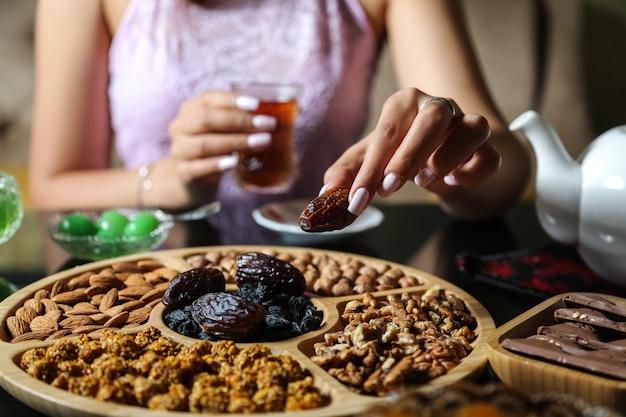 Bovenaanzicht vrouw eten van droge kaki met thee en mix van noten en chocolade op tafel