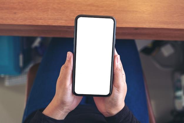 Bovenaanzicht vrouw handen met zwarte mobiele telefoon met leeg wit scherm zittend op een stoel