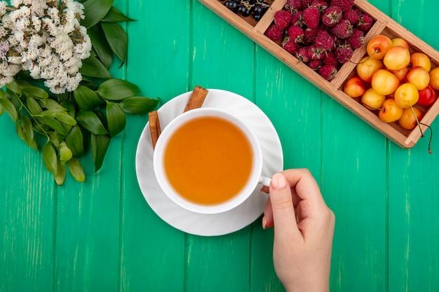 Bovenaanzicht vrouw houdt kopje thee met kaneel frambozen en witte kersen op een groene tafel