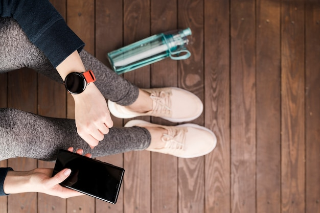 Bovenaanzicht vrouw in sportkleding bedrijf mobiele telefoon