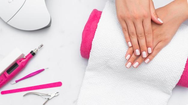 Bovenaanzicht vrouw krijgt haar manicure gedaan in de salon