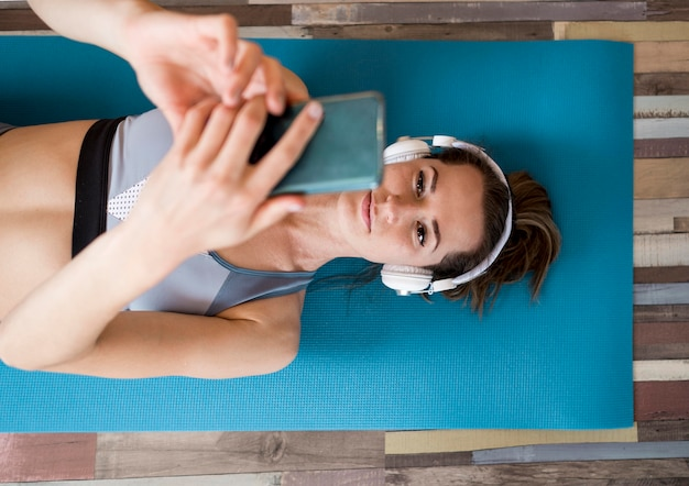 Bovenaanzicht vrouw luisteren naar muziek op yogamat
