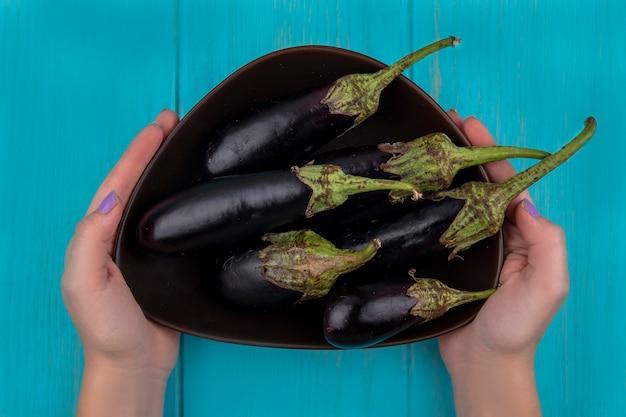 Bovenaanzicht vrouw met aubergine in kom op turkooizen achtergrond