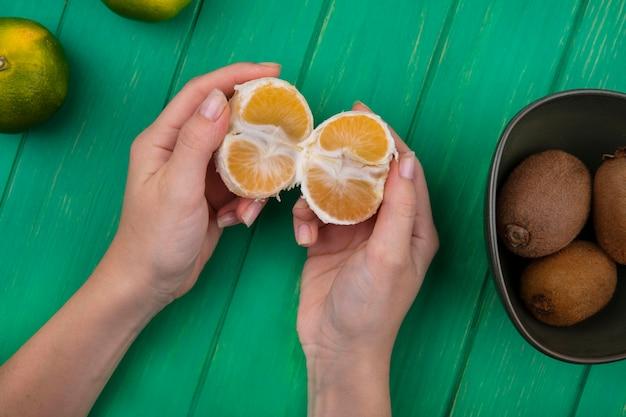 Bovenaanzicht vrouw met gepelde mandarijn in haar handen met kiwi in een kom op een groene muur