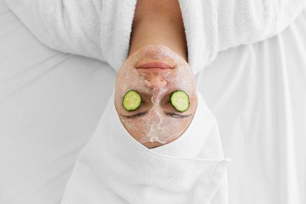 Bovenaanzicht vrouw met gezichtscrème en komkommers