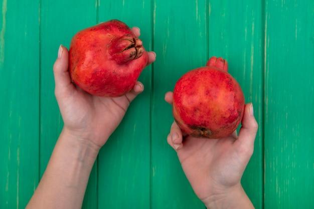 Bovenaanzicht vrouw met granaatappels in handen op groene muur