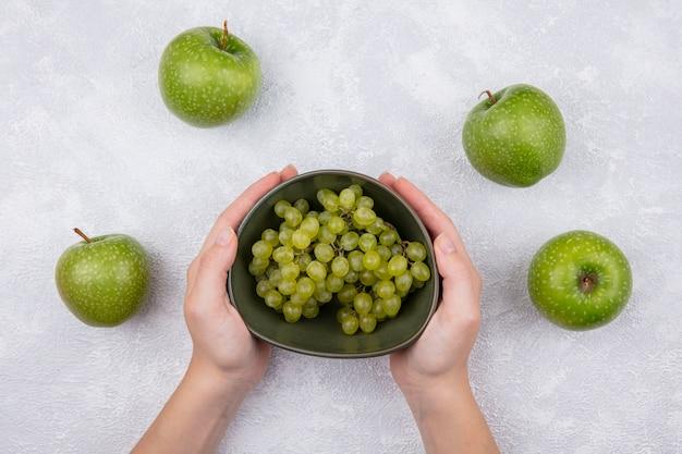 Bovenaanzicht vrouw met groene druiven in een kom met groene appels op een witte achtergrond