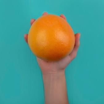 Bovenaanzicht vrouw met in de hand grapefruit op turkooizen achtergrond