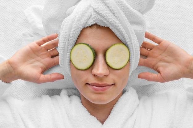 Bovenaanzicht vrouw met plakjes komkommer