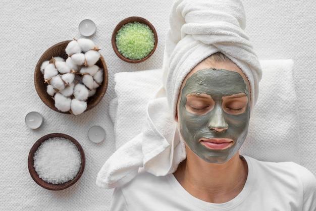 Bovenaanzicht vrouw ontspannen met gezichtsmasker