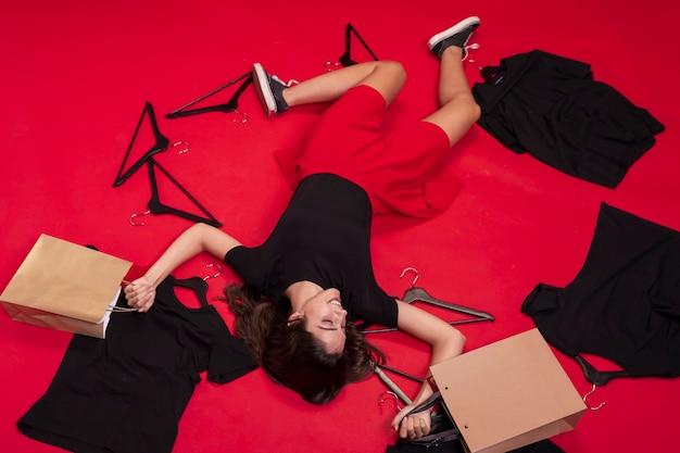 Bovenaanzicht vrouw op de vloer blijven met haar nieuwe kleren