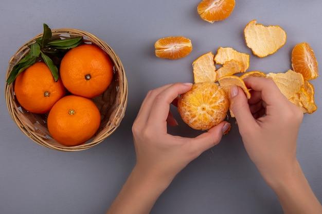Bovenaanzicht vrouw pelt sinaasappel uit schil met mandje op grijze achtergrond