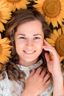 Bovenaanzicht vrouw poseren in zonnebloem veld