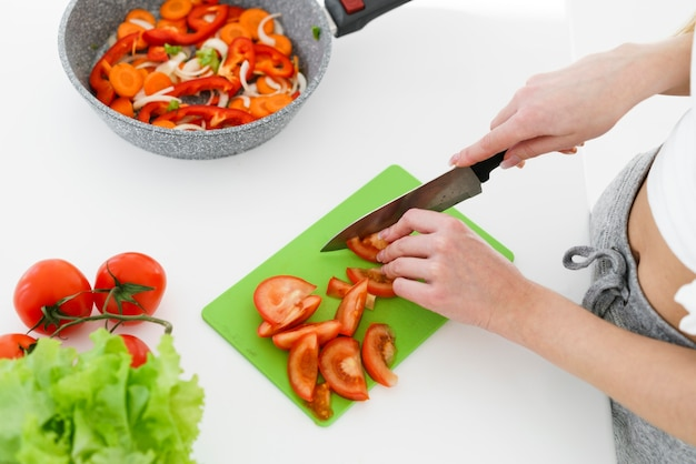 Bovenaanzicht vrouw snijden tomaten