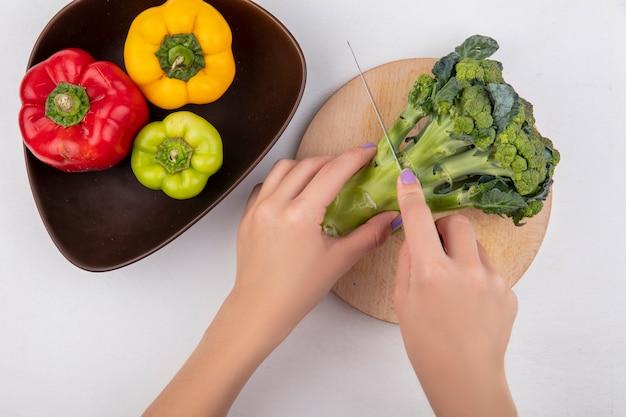 Bovenaanzicht vrouw snijdt broccoli op een snijplank met gekleurde paprika in een kom op een witte achtergrond