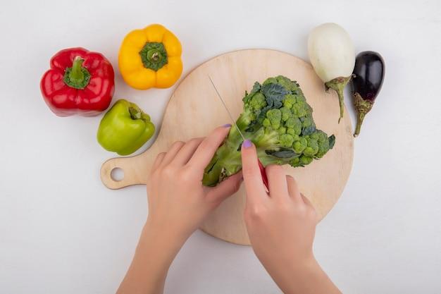 Bovenaanzicht vrouw snijdt broccoli op snijplank met gekleurde paprika en aubergines op witte achtergrond