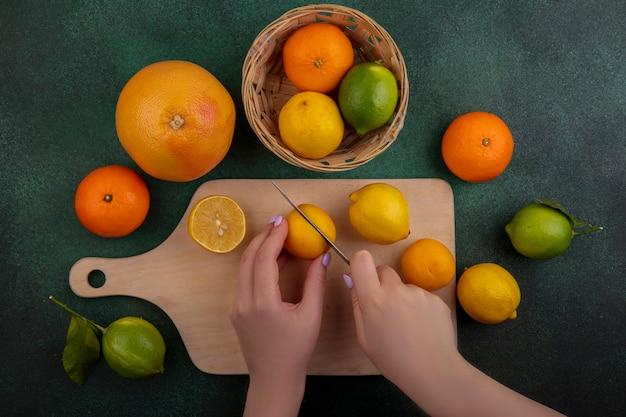 Bovenaanzicht vrouw snijdt citroenen op snijplank met limoenen sinaasappelen en grapefruit op groene achtergrond