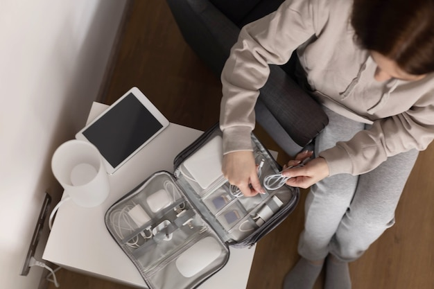 Bovenaanzicht vrouw zet draden tablet moderne elektronische apparaatapparatuur in comfortabele opbergtas